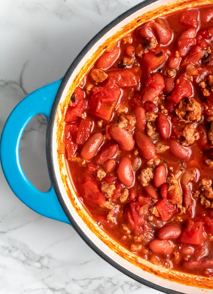 A blue dutch oven of gluten-free chili on a marble surface