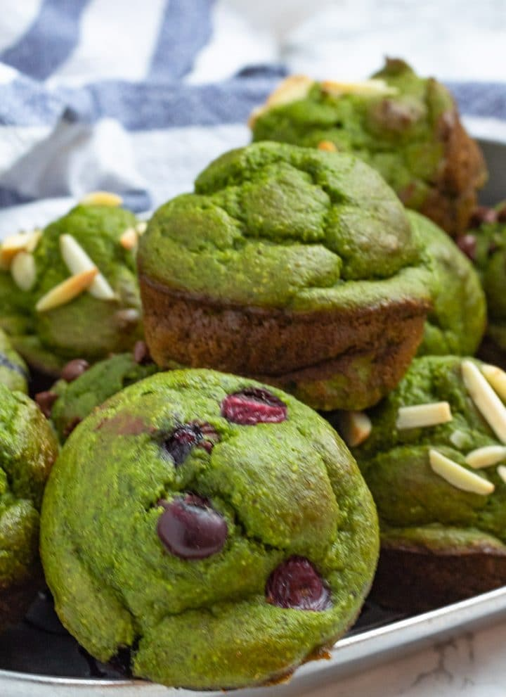 green spinach banana muffins on a metal tray - some with almonds, some plain, some with blueberries