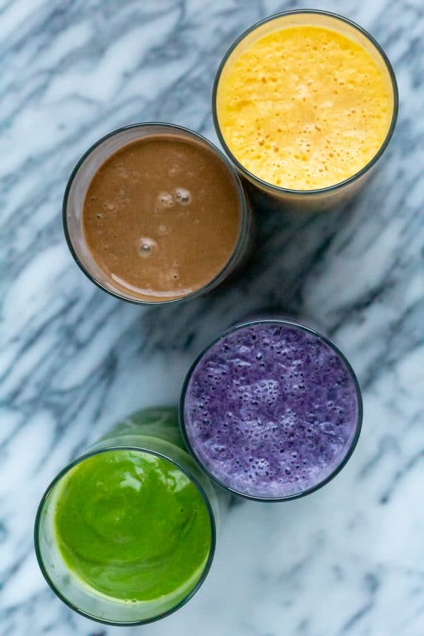 overhead shot of purple, yellow, green and brown smoothies
