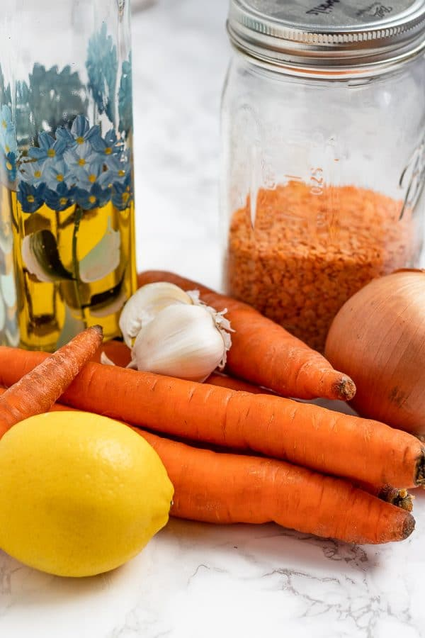 ingredients needed for carrot and lentil soup: olive oil, red lentils, carrots, garlic, onion, and lemon
