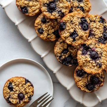 baked oatmeal cups with blueberries on a ceramic plattern with one on a small plate with a fork