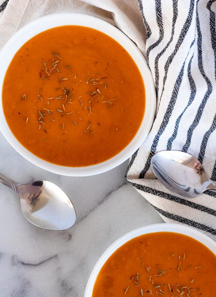 two white bowls of creamy, dark orange roasted savory butternut squash soup garnished with dried thyme